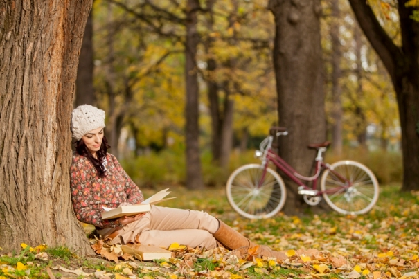 Young woman reading in the autumn forest